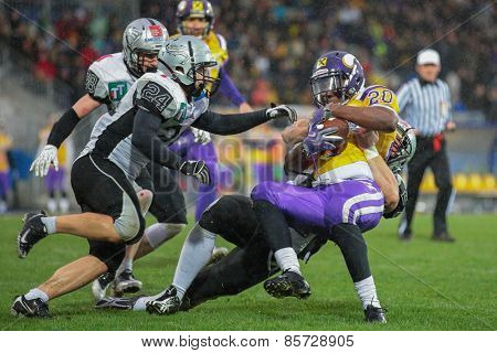 VIENNA, AUSTRIA - MARCH 23, 2014: RB Islaam Amadu (#20 Vikings) is tackled by DB Patrick Pilger (#20 Raiders) in an AFL football game.