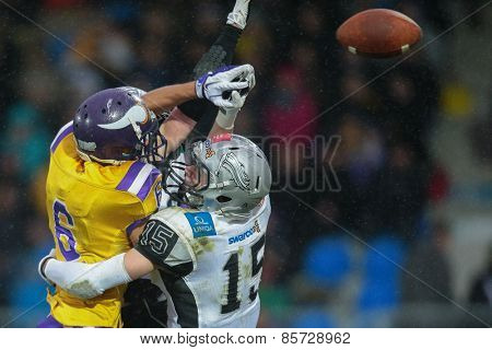 VIENNA, AUSTRIA - MARCH 23, 2014: DB Simon Unterrainer (#15 Raiders) and WR Laurinho Walch (#6 Vikings) fight for the ball in an AFL football game.
