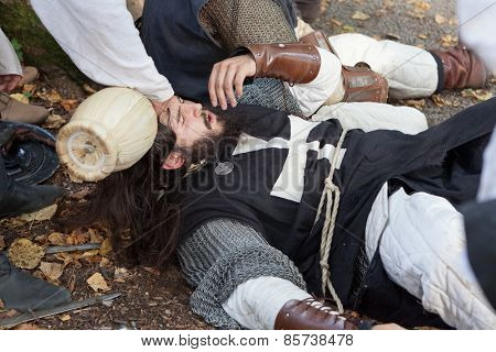 ZAGREB, CROATIA - OCTOBER 07, 2012: Squire helping tired knight with a splash of water after the battle at