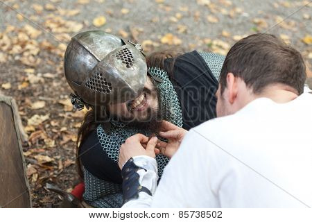 ZAGREB, CROATIA - OCTOBER 07, 2012: Squire helping injured knight to remove his helmet at