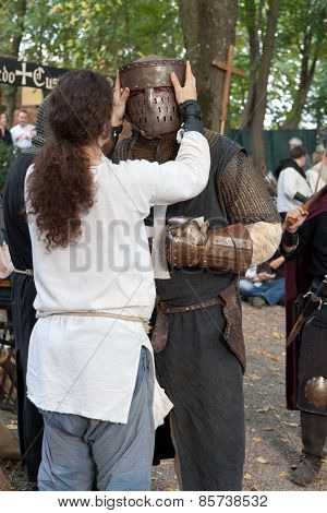 ZAGREB, CROATIA - OCTOBER 07, 2012: Squire helping the knight to get ready for battle at