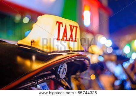 Thai Taxi (tuk Tuk) Sign With Defocused Lights Blur , Chiang Mai, Thailand.