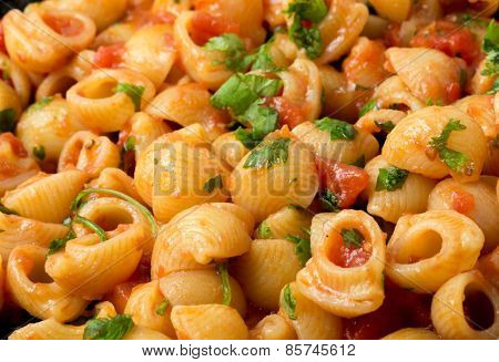 Gomiti elbow pasta shells in arrabbiata tomato, garlic and chili sauce, garnished with chopped parsley, cooking in a frying pan. poster