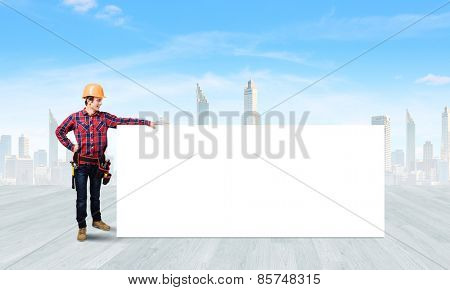 Young smiling craftsman holding with blank banner. Place for text poster