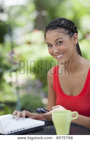 Beautiful Young Woman Using a Cellphone and Laptop Outdoors