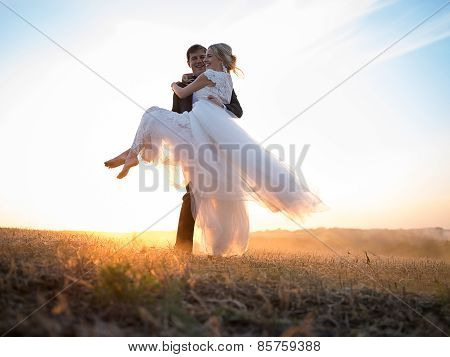 Husband carries his beloved wife in arms