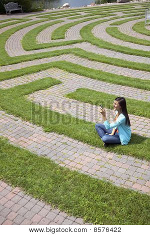 Young Woman Text Messaging in a Grass Maze