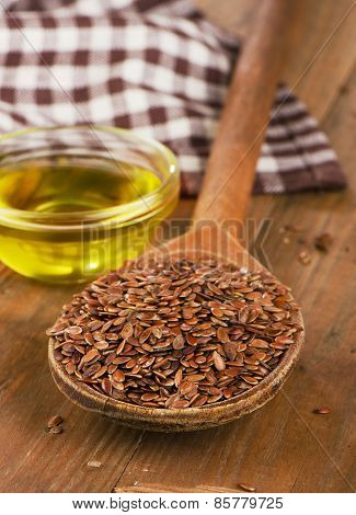 Brown Flax Seeds On Spoon And Flaxseed Oil