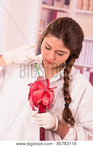 beautiful female biologist experimenting with red flower