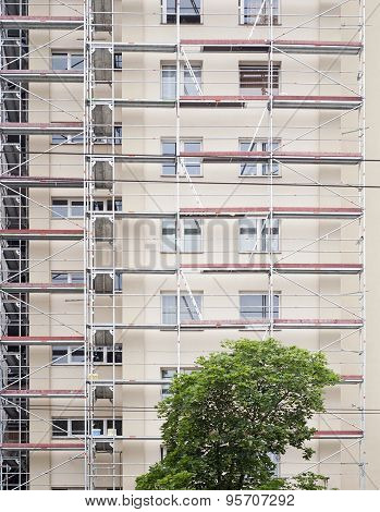 restoration facade of tall house, scaffolding construction poster