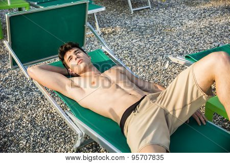 Shirtless Young Man Drying Off in Hot Sun, Muscular Man Wearing Bathing Suit  Sunbathing on Beach Lounge Chair on Grass poster