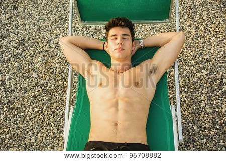 Shirtless Young Man Sunbathing in Lounge Chair on Beach
