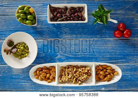 Mediterranean tapas black olives capers and nuts on blue wood table