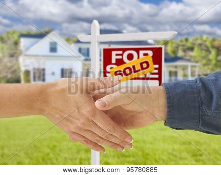 Man and Woman Shaking Hands in Front of a Beautiful New House and Sold For Sale Real Estate Sign.