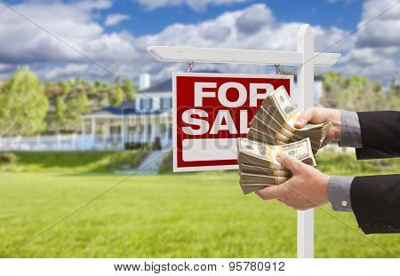 Man Handing Over Thousands of Dollars in Front of House and For Sale Real Estate Sign.