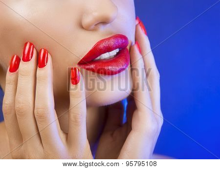 Beautiful Sexy Young Girl With Red Lips And Red Nail Polish, Bright Make-up On Blue Background