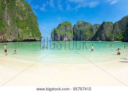 MAYA BAY, THAILAND - FEBRUARY 24, 2012: Visitors wade into the bright blue shallows of Maya Bay, one of the iconic beaches of Southern Thailand.