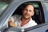 Middle age man smile into camera in his car from front seat, driver seat. poster
