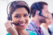 Close up plan of a smiling businesswoman in a call centre poster