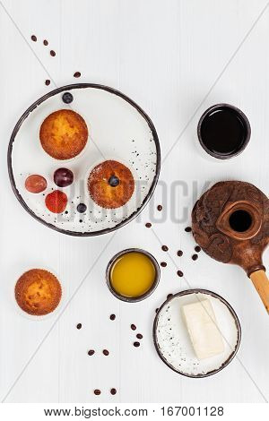 Little morning fest. Nutritious beautiful morning meal consisting of muffins, berries, cheese and drinks arranged neatly on white wooden table