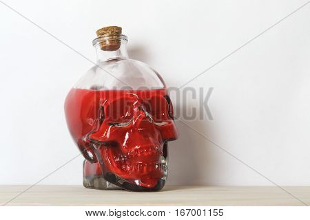 Human skull containing blood or poison a symbol of death horror and vanitas.
