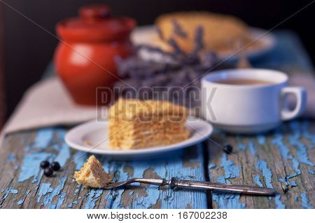 A cup of tea and a honey lavender with lavender on a wooden blue background. Homemade cake baking cup of tea lavender wooden background