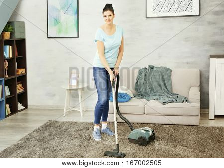 Cleaner hoovering carpet in room