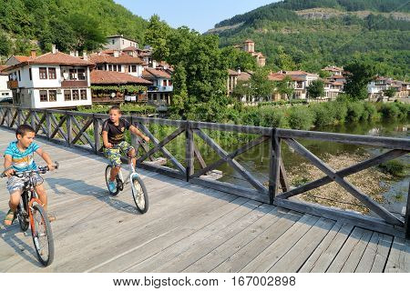 VELIKO TARNOVO, BULGARIA - JULY 30, 2015: Two young boys crossing a wooden bridge by bicycle on the Yantra river