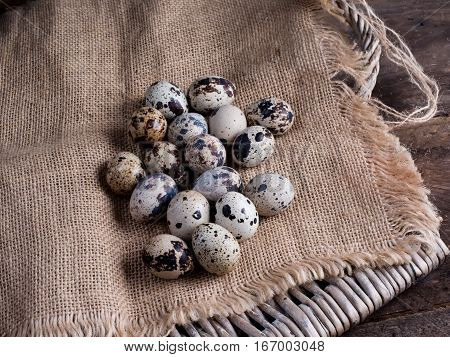 Quail eggs on sacking and wooden background
