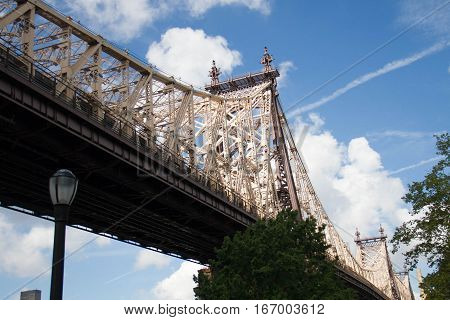 Queensboro bridge, trees and light pole with cloudy blue sky, New York