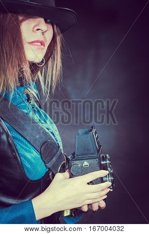 Photography and retro style. Young vintage attractive girl holds old aged camera. Steampunk photographer taking photo.