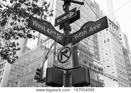 West 42nd Street, Fifth Ave, One way, No turn signs and traffic light on the pole in black and white style, Manhattan, New York