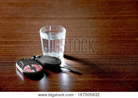 Glass of alcoholic beverage and car key on table. Don't drink and drive concept