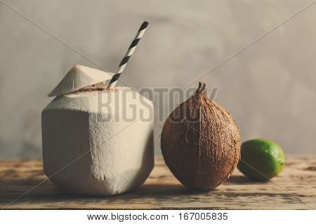 Coconut cocktail with straw and nut on wooden table