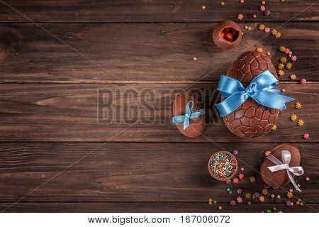 Chocolate Easter eggs with color ribbon bow on wooden background