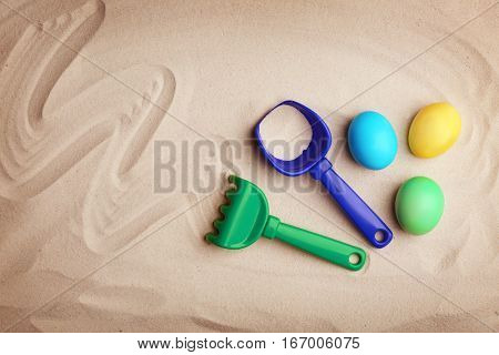 Easter eggs with rake on sand