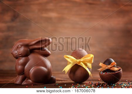 Chocolate Easter bunny with eggs on wooden background