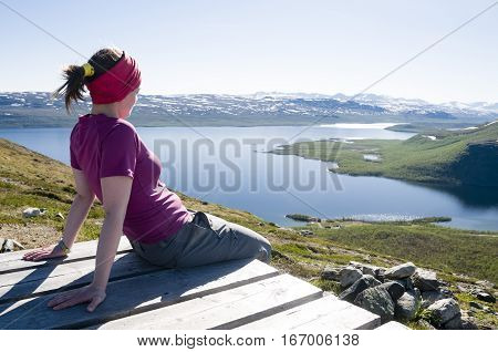 Girl sitting on the top of Saana Fell and looking down at Lake Kilpisjarvi and surrounding area. Kilpisjarvi Finnish Lapland Finland Europe