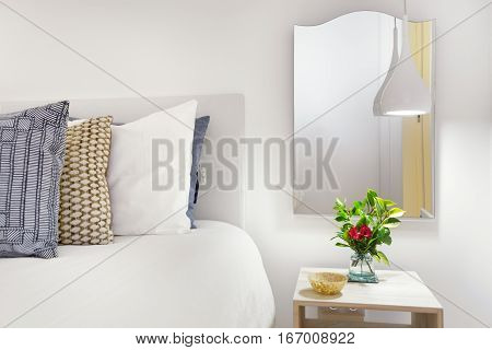 A Modern Nightstand With Lamp and Flower Arrangement