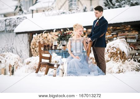 Winter wedding outdoors on background of snow-covered house. Bride sits on a chair groom stands close by. Beside them is chair and table with goblets of wine and bouquet.