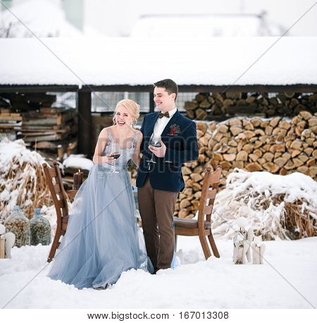 Winter wedding outdoor on snow and firewood background. Bride and groom stand near table with goblets of wine. They laugh fun.