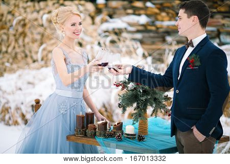 Winter wedding outdoor on table and firewood background. Bride and groom stand near table and clink glasses with wine. Beside them is table with bouquet.