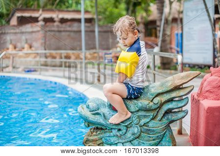 A Boy Sits On The Asian Statue