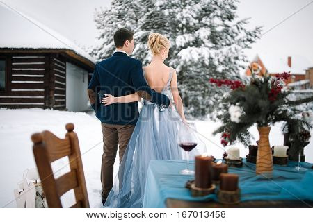 Winter wedding outdoors on background of snow-covered house and fir. Bride and groom are standing with their back and hugging. On the table are standing goblets with wine burning candles and bouquet.