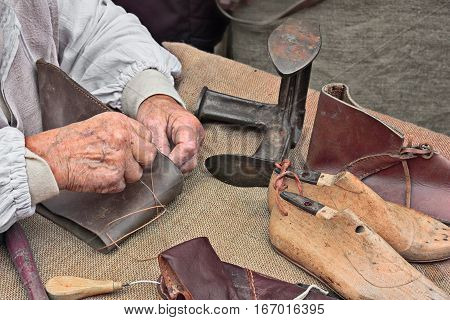 elderly shoemaker makes artisan shoes on an old bench with tools for leather working