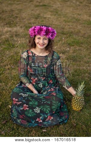 Happy curvy girl with a pineapple and a flower crown in the landscape