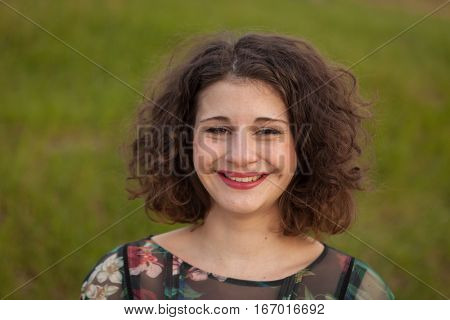 Happy curvy girl with curly hair in the landscape with a flowered dress