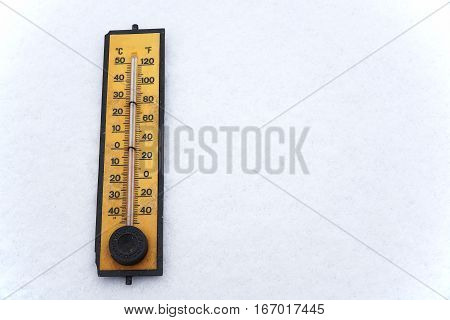 close up on old thermometer on white snow background