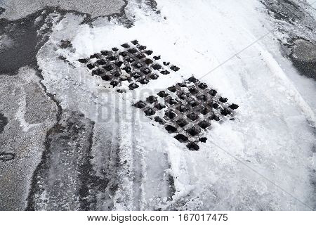 snow and ice on manhole and asphalt road surface
