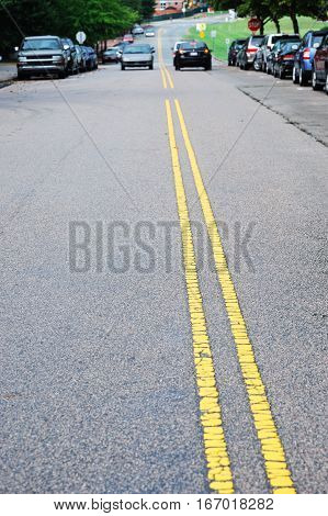 double yellow line in urban street with cars parking along the street